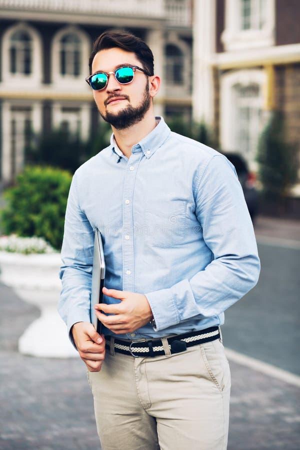 Homem de negócios farpado considerável da vista vertical nos óculos de sol que anda em torno do quarto britânico Guarda o portáti imagens de stock