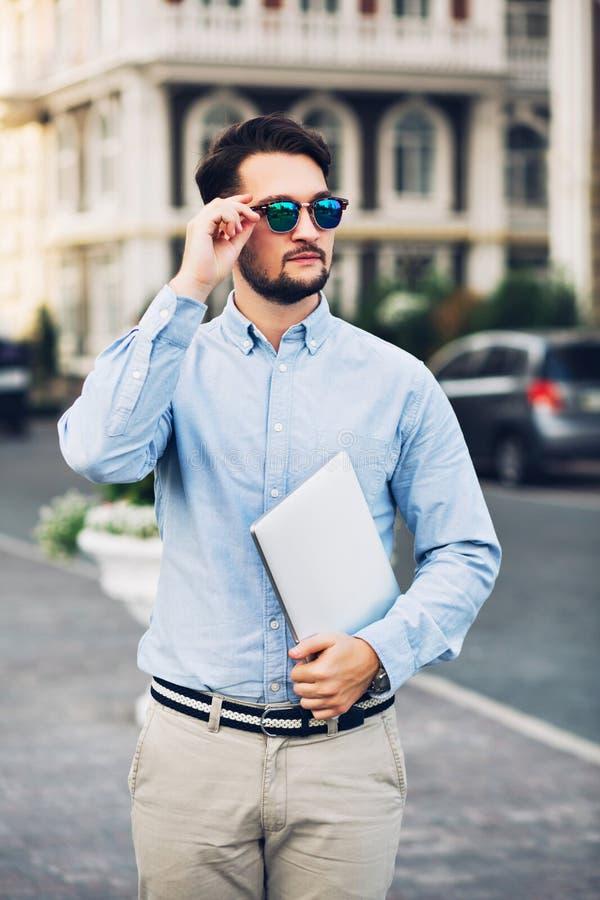 Homem de negócios farpado da vista vertical nos óculos de sol que anda na rua na cidade Guarda o portátil, olhando seriamente lon imagem de stock