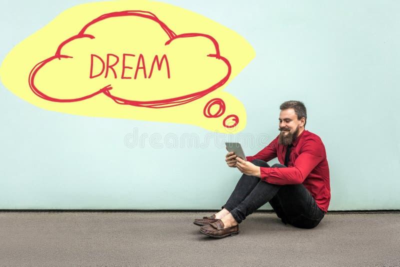 Homem de neg?cios farpado feliz na camisa vermelha que senta-se no assoalho, guardando, olhando sua tabuleta digital e sonhando,  foto de stock royalty free