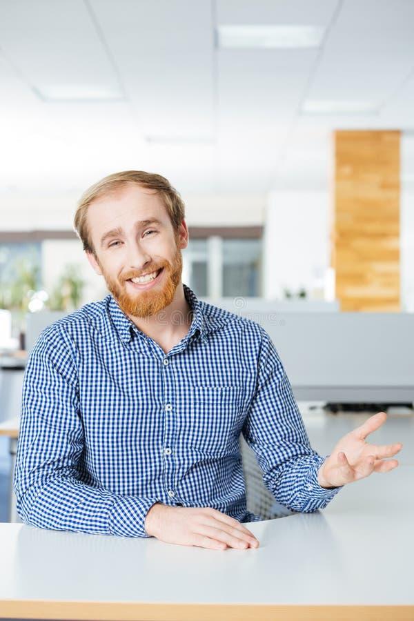 Homem de negócios farpado feliz que fala e que sorri no escritório fotos de stock royalty free