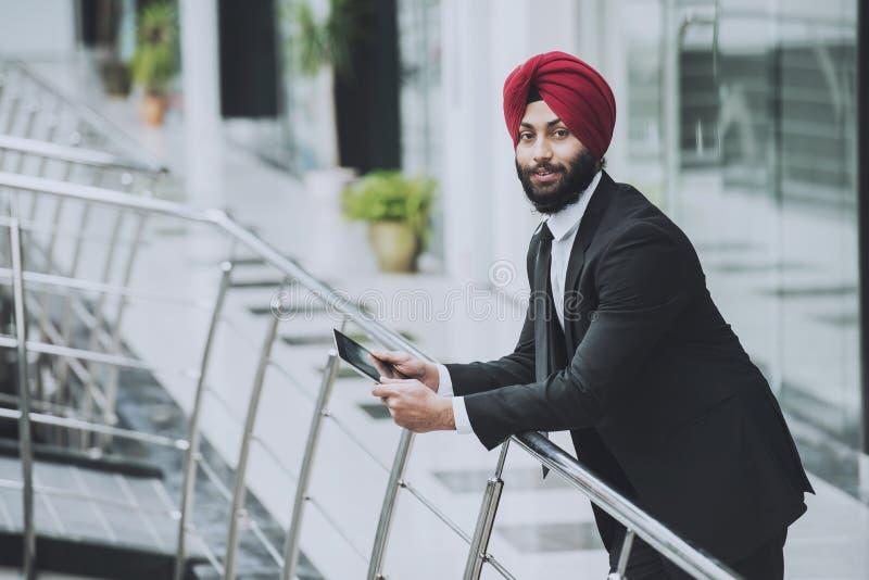Homem de negócios farpado indiano novo no escritório moderno imagens de stock
