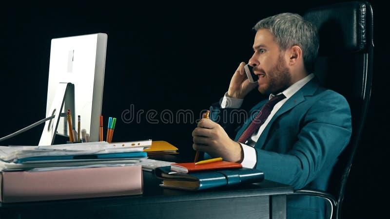 Homem de negócios farpado irritado que tem a conversação fatigante emocional em seu telefone celular Fundo preto foto de stock