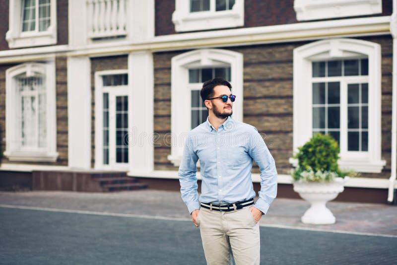 Homem de negócios farpado nos óculos de sol que anda na rua Guarda as mãos em uns bolsos, sorrindo longe fotografia de stock
