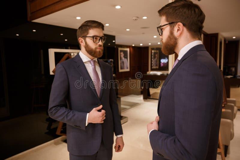 Homem de negócios farpado novo concentrado que está dentro fotos de stock