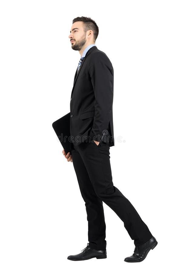 Homem de negócios farpado novo no terno que guarda a pasta de arquivos com opinião lateral de passeio da documentação imagem de stock royalty free