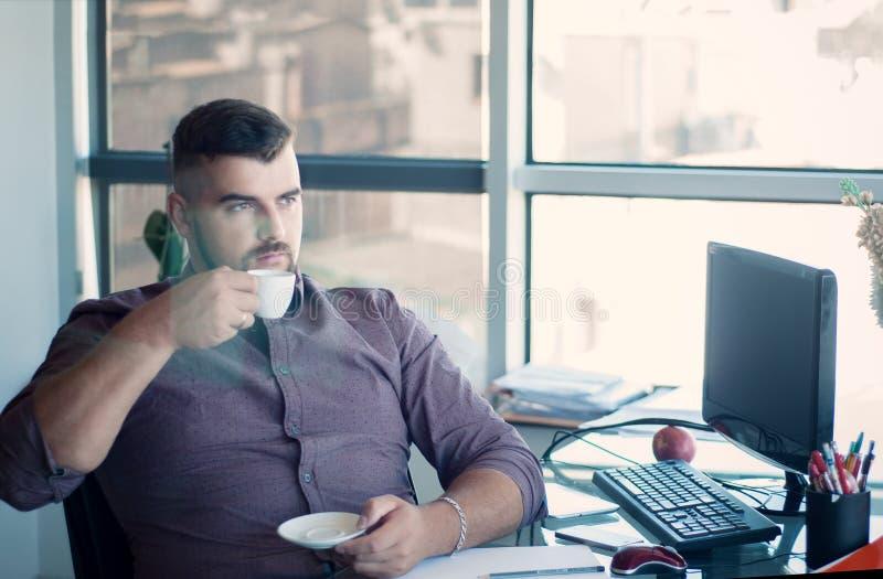 Homem de negócios farpado pensativo que tem a ruptura, café bebendo em imagem de stock royalty free