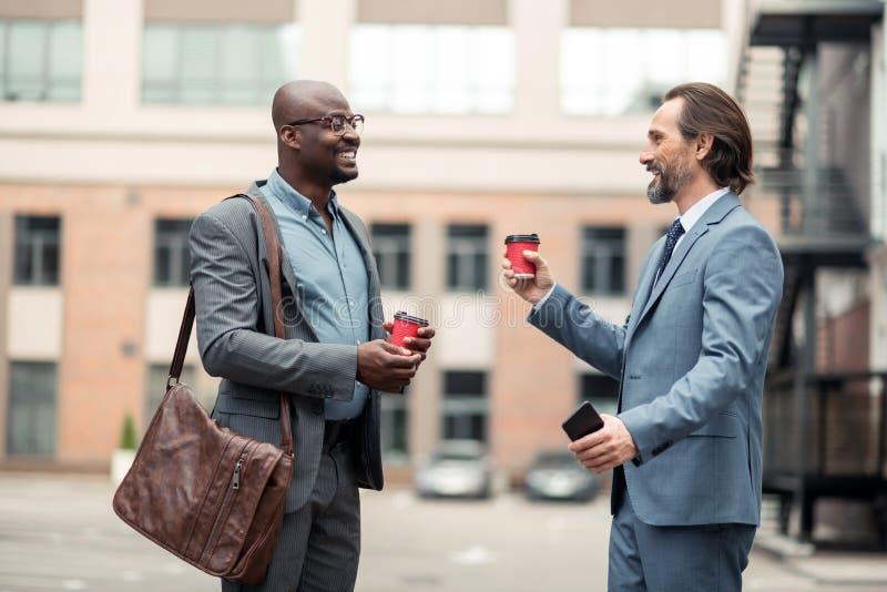 Homem de negócios farpado que fala com o colega e o café bebendo fotos de stock