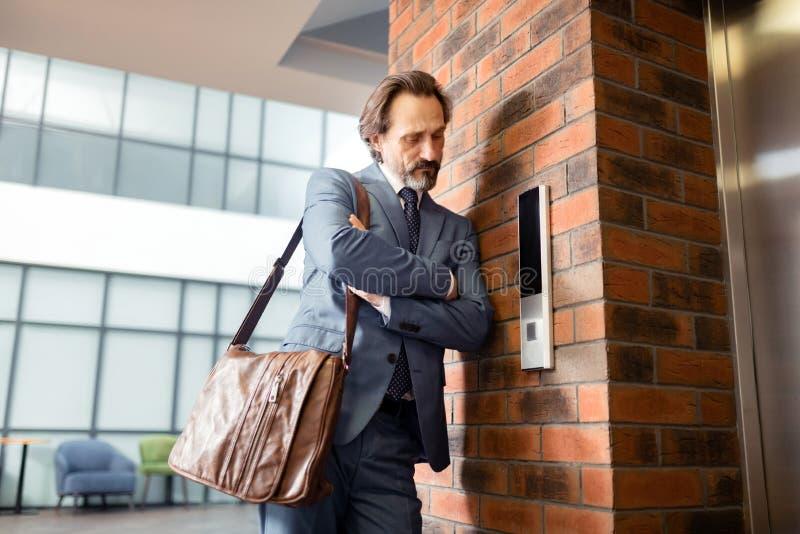 Homem de negócios farpado que odeia a espera perto do elevador fotografia de stock royalty free