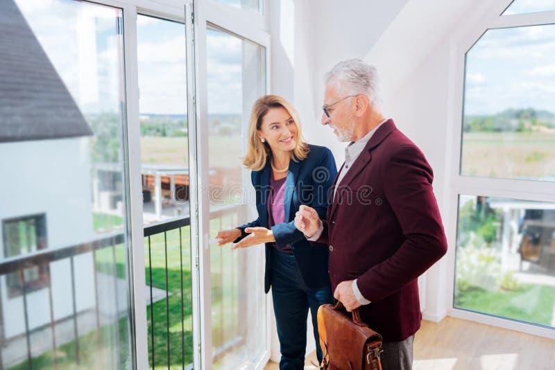 Homem de negócios farpado que veste o revestimento elegante que hesita sobre a compra da casa nova fotos de stock royalty free