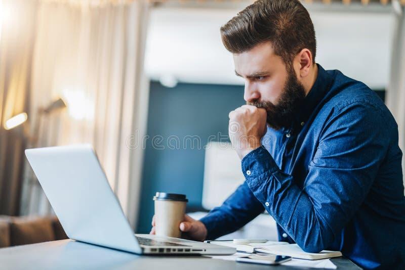 Homem de negócios farpado sério que trabalha no computador, café bebendo, pensando O homem analisa a informação, verificando o em fotos de stock