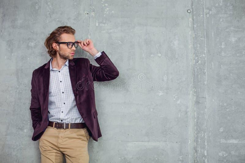Homem de negócios farpado seguro que inclina-se contra a parede imagens de stock