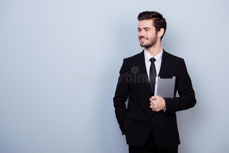 Homem de negócios feliz bem sucedido novo considerável no holdin preto do terno imagem de stock royalty free