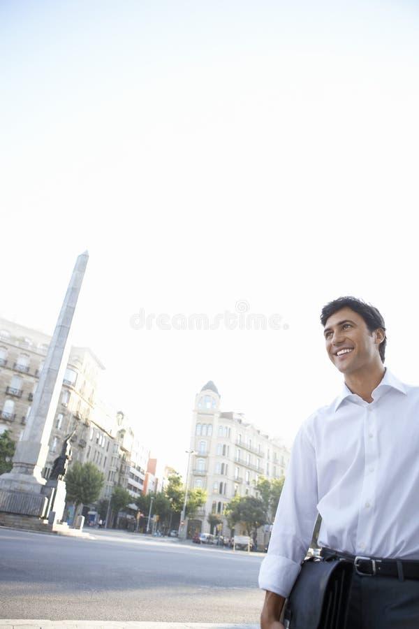 Homem de negócios feliz With Briefcase Looking afastado na rua da cidade foto de stock royalty free