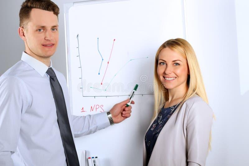 Homem de negócios feliz com a mulher de negócios que dá uma apresentação no flipchart Conceito dos trabalhos de equipa imagem de stock royalty free