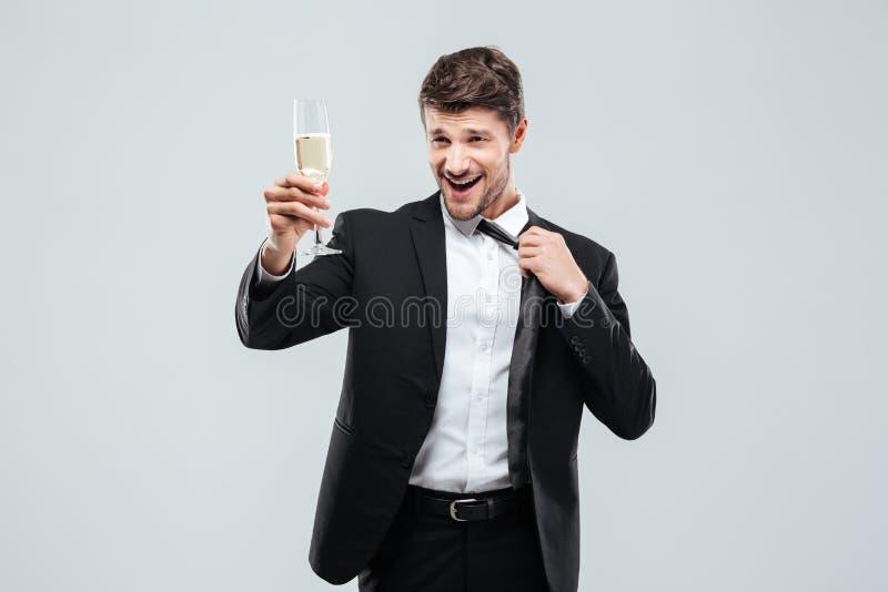 Homem de negócios feliz com o vidro do chamagne que está e que faz elogios imagens de stock royalty free