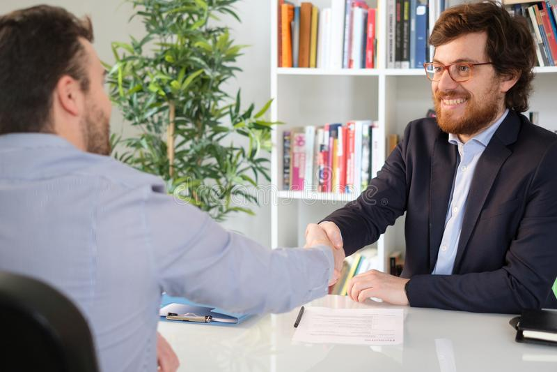 Homem de negócios feliz com um negócio do closing do cliente fotografia de stock royalty free