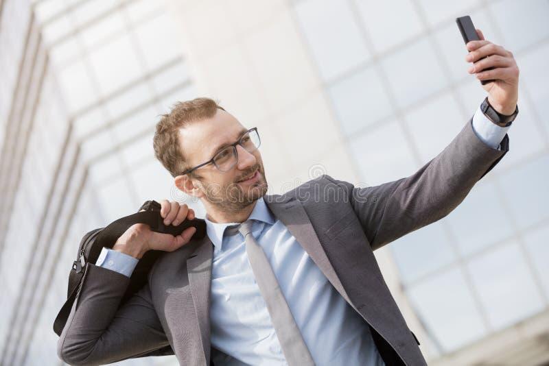 Homem de negócios feliz com um saco sobre seu ombro que remove o selfie fotografia de stock royalty free