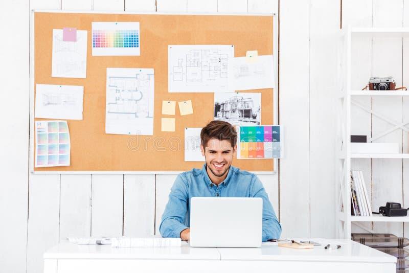 Homem de negócios feliz considerável que trabalha com o portátil no escritório imagens de stock