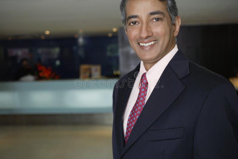 Homem de negócios feliz At Hotel Lobby fotografia de stock