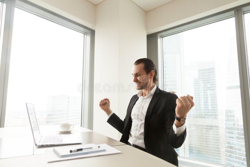 Homem de negócios feliz na frente do portátil que comemora o achi impressionante fotos de stock