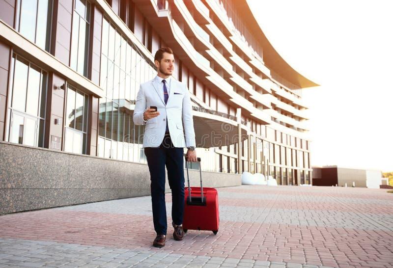 Homem de negócios feliz novo do viajante que faz a chamada após a chegada no hotel fora com sua bagagem foto de stock royalty free