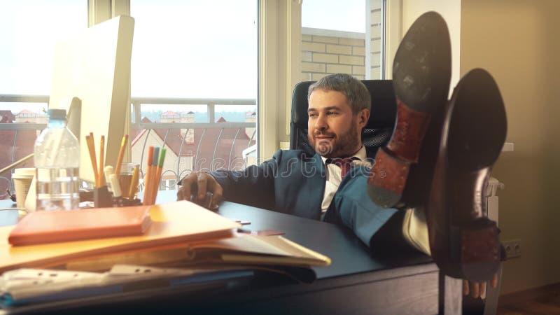 Homem de negócios feliz novo que relaxa em seu local de trabalho e que põe seus pés sobre a mesa fotografia de stock royalty free