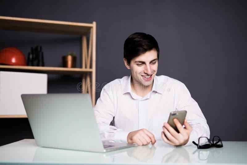 Homem de negócios feliz novo que sorri ao ler seu smartphone Retrato da mensagem de sorriso da leitura do homem de negócio com sm imagens de stock