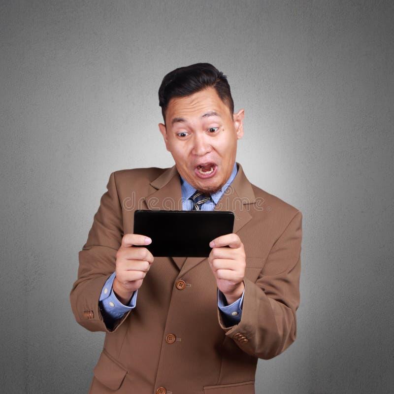 Homem de negócios feliz Playing em sua tabuleta fotografia de stock