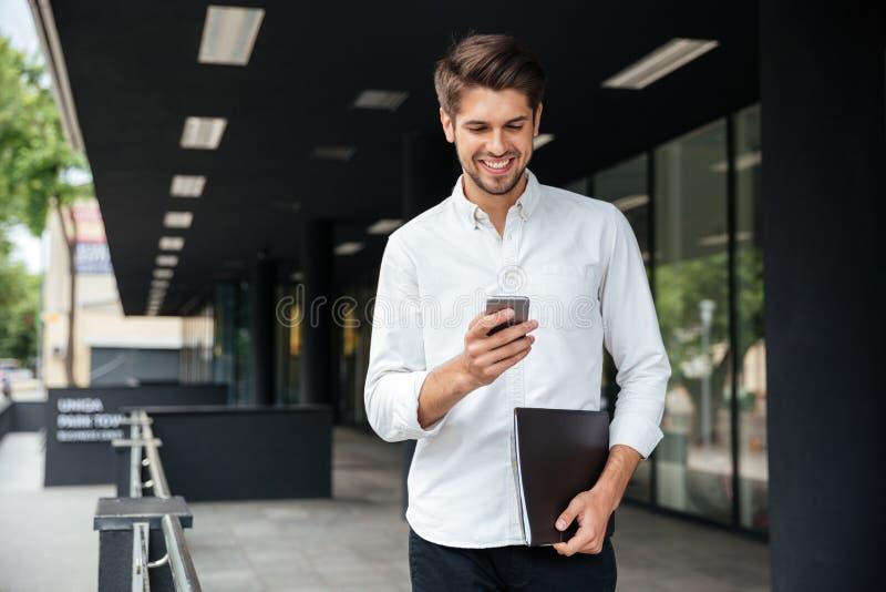 Homem de negócios feliz que anda e que usa o telefone celular fora fotos de stock