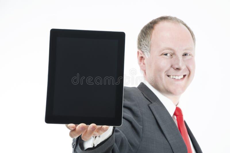 Homem de negócios feliz que apresenta (sth sobre) a tabuleta digital foto de stock royalty free