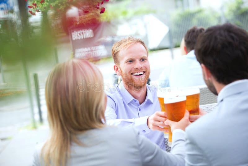Homem de negócios feliz que brinda o vidro de cerveja com os colegas no restaurante exterior imagens de stock royalty free