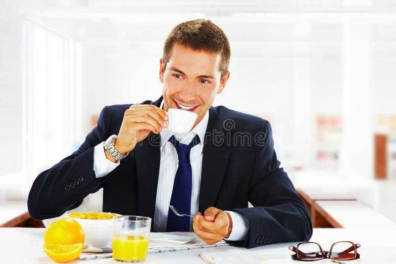 Homem de negócios feliz que come o pequeno almoço no escritório fotos de stock royalty free