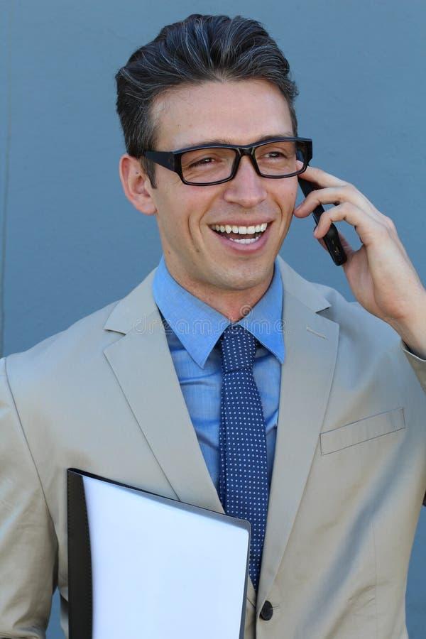 Homem de negócios feliz que fala no telefone com o dobrador à disposição isolado sobre o fundo azul no tiro do estúdio foto de stock