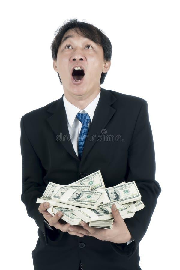 Homem de negócios feliz que guarda muitos dólares americanos em sua mão fotos de stock royalty free