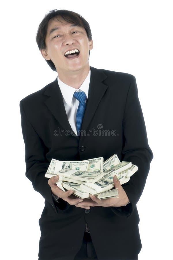 Homem de negócios feliz que guarda muitos dólares americanos em sua mão foto de stock royalty free