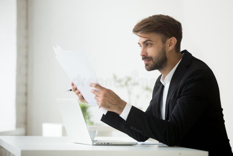 Homem de negócios feliz que guarda os papéis que leem estatísticas financeiras fotos de stock