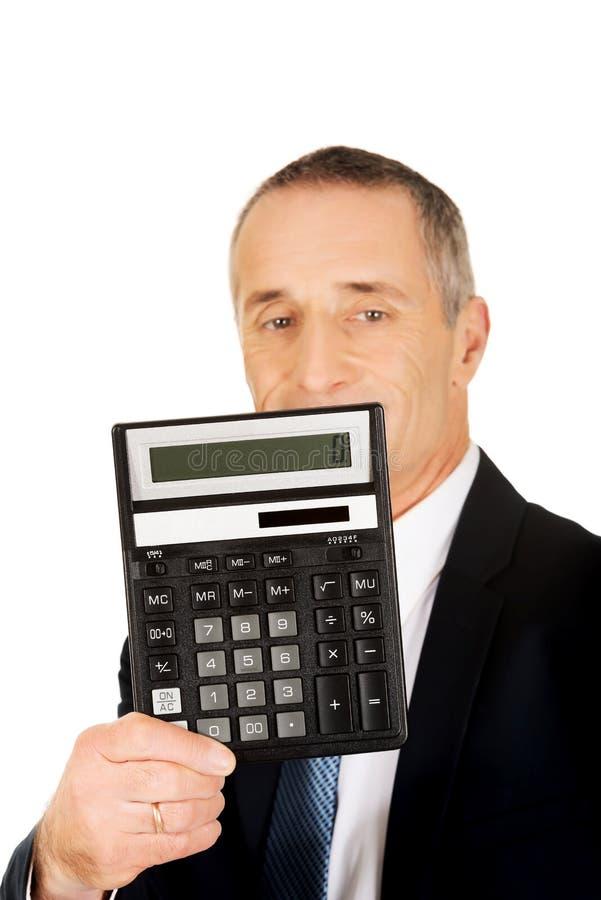 Homem de negócios feliz que guarda uma calculadora fotografia de stock