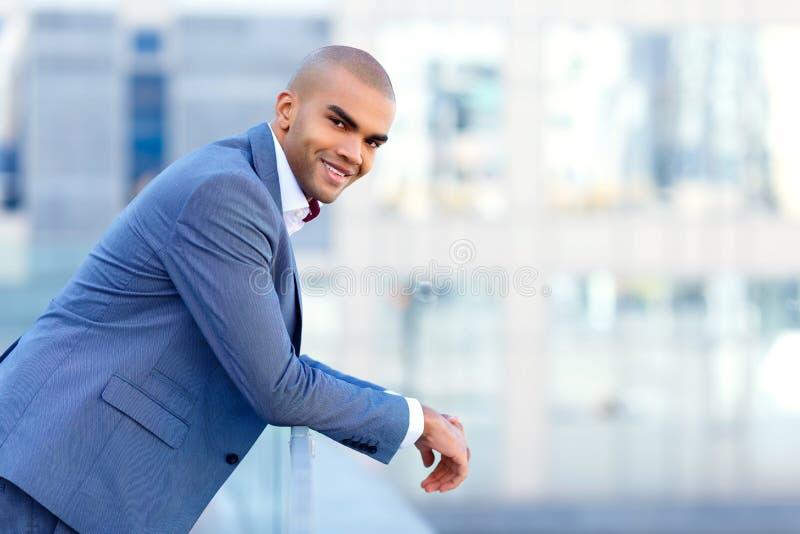 Homem de negócios feliz que inclina-se no corrimão imagens de stock