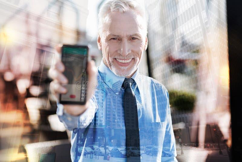 Homem de negócios feliz que mostra seus smartphone e sorriso surpreendentes novos fotografia de stock
