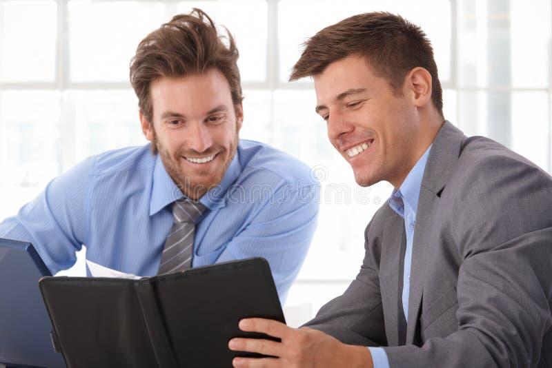 Homem de negócios feliz que olha o organizador pessoal fotografia de stock royalty free