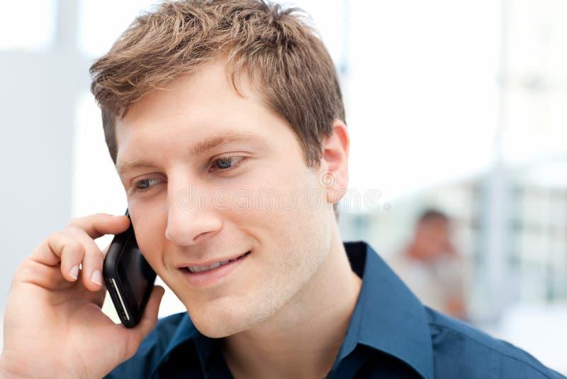 Homem de negócios feliz que telefona em seu escritório imagens de stock royalty free