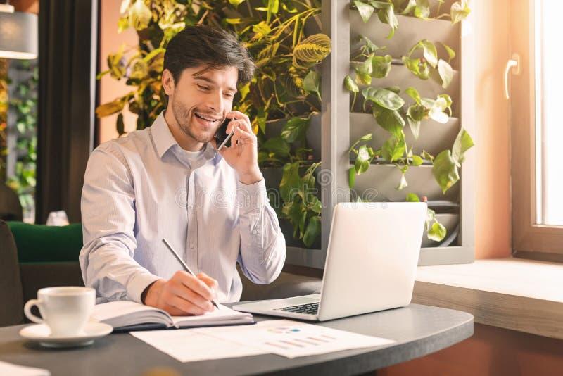 Homem de negócios feliz que tem a conversação do smartphone no café imagem de stock royalty free