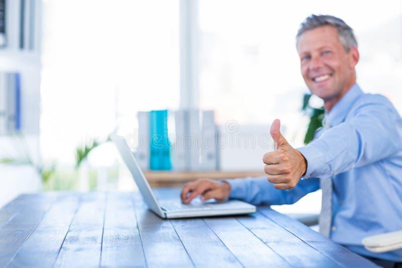 Homem de negócios feliz que usa o laptop e olhando a câmera com polegares acima fotografia de stock royalty free