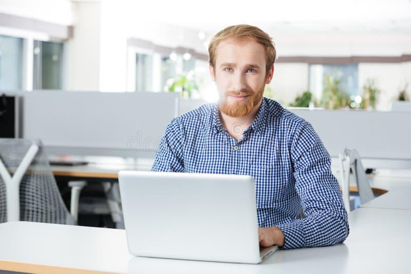 Homem de negócios feliz que usa o portátil no local de trabalho no escritório imagens de stock royalty free