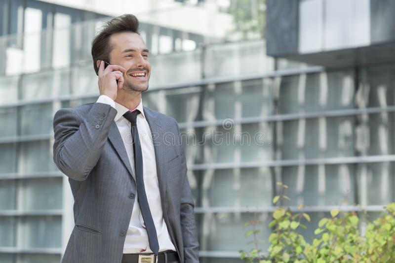Homem de negócios feliz que usa o telefone celular fora do escritório fotos de stock royalty free