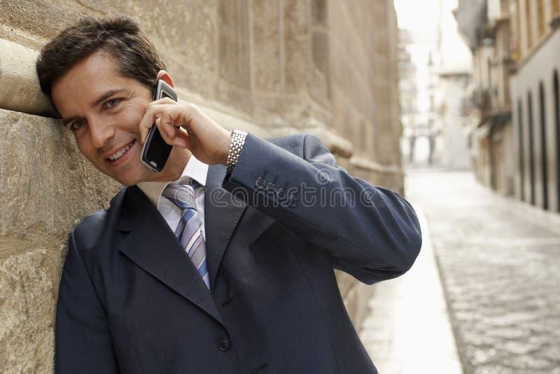 Homem de negócios feliz Using Mobile Phone na rua fotografia de stock