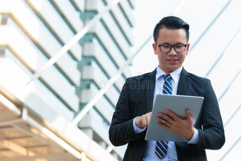 Homem de negócios feliz vestido no terno preto usando a tabuleta digital fora do escritório e do sorriso Conceito da tecnologia d fotografia de stock