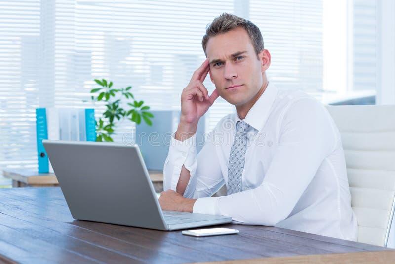 Homem de negócios focalizado que olha a câmera imagem de stock