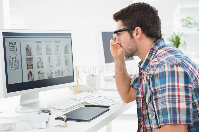 Homem de negócios focalizado que usa o monitor do computador fotos de stock