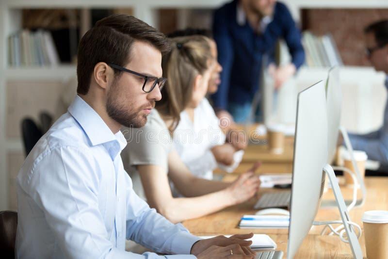 Homem de negócios focalizado sério que olha a tela de monitor imagem de stock royalty free